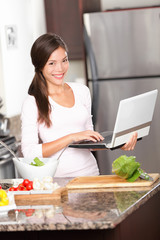 Kitchen woman on laptop reading online cooking recipes