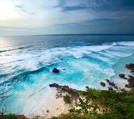 Coast of Indian ocean with waves and cloudy sky. Bali, Indonesia