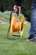 Gärtner schleppt Kabeltrommel über Rasen bunt