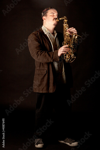 Jazzman playing saxophone with eyes closed on dark background