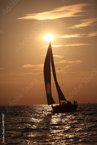Yacht and sails against the sunset sky