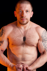 Muscular shirtless male with dog tags over black background
