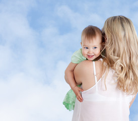 Rear view of mother with cute baby girl looking over shoulder