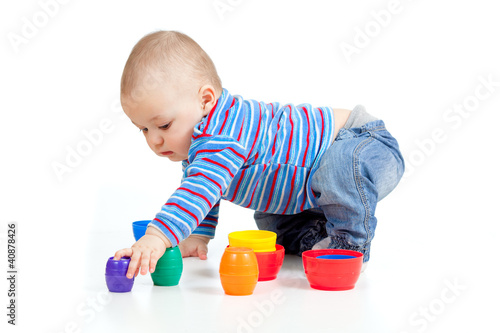 baby playing with colurful cup toys on floor, isolated over whit