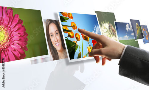 touchscreen interface: man hand reaching images on the screen