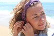 Young curly hair woman putting on earring