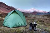 Zelt und Wanderschuhe vor dem Sonnenaufgang