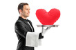 A portrait of a waiter holding a tray with a red heart shape on