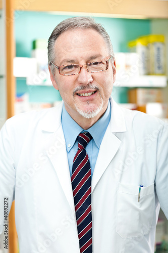 Handsome senior chemist in his store smiling
