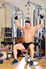 Young bodybuilder training in the gym. Back muscles, front wiew