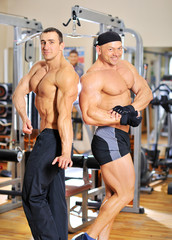 Two bodybuilders posing at the gym