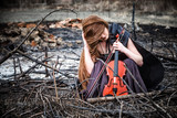 The red-haired girl with a violin sitting on ashes