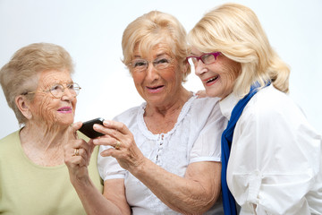 Elderly female friends with mobile device.