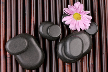 Spa stones and flower on bamboo mat