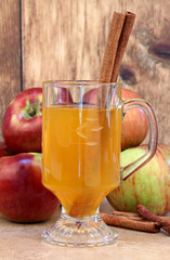 Apple cider with cinnamon sticks and apples.