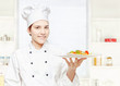 chef holding vegetarian meal in kitchen