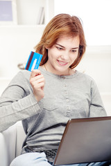 Happy girl doing on line shopping with credit card
