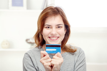 Happy young woman holding credit card