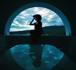 Woman's silhouette in window opening.