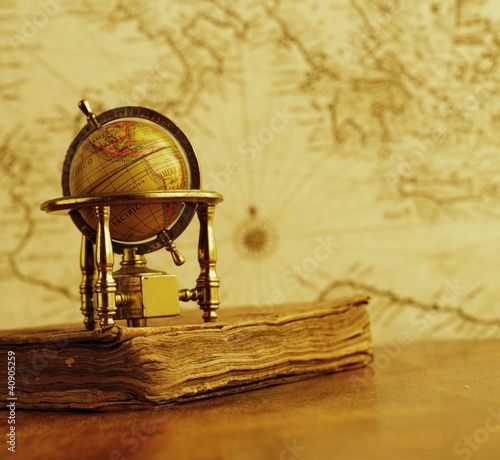 Globe and vintage book against map on a wall.