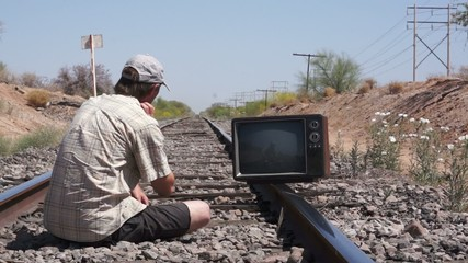 Sitting on the Railway Tracks with an Old, Retro Television