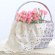Delicate pink carnations in a white wicker basket