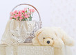 Still life with teddy bear, wicker basket and pink flowers
