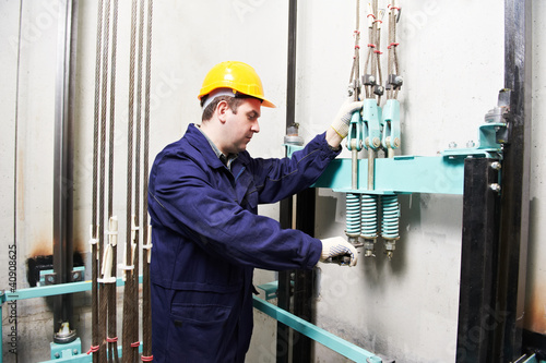 machinist with spanner adjusting lift mechanism - 40908625