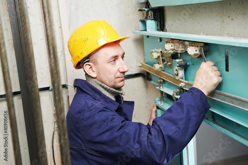 Leinwandbild Motiv machinist with spanner adjusting lift mechanism