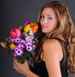 Young, beautiful woman with a colorful bouquet of spring flowers