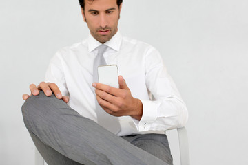 Businessman reading short message on mobile phone