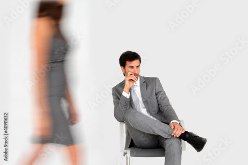Businessman sitting in waiting room and woman walking by