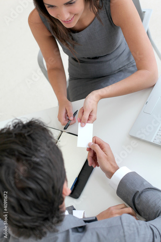 Upper view of hands holding business card