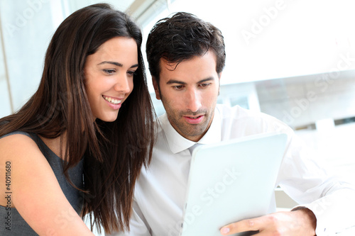 Business people websurfing on tablet during breaktime
