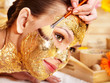 Woman getting  gold facial mask .