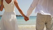 Closeup shot of a couple holding hands on the beach