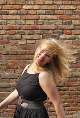Blonde Frau wirft ausgelassen ihre Haare