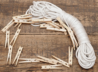 clothespins on rope on wooden background