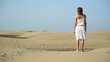 Woman in white dress standing in the desert