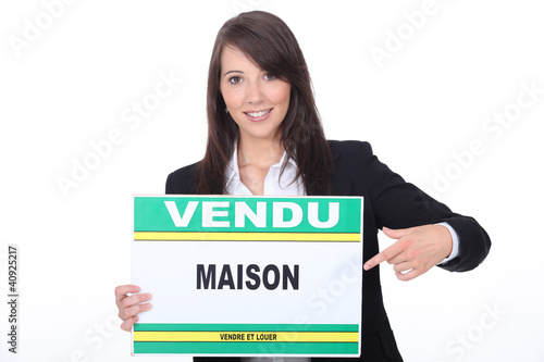 French Estate Agent with a 'Vendu' sign