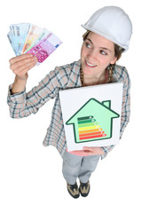 portrait of cute female heating engineer holding bank notes