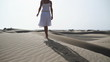Woman in white dress and summer hat walking on the beach