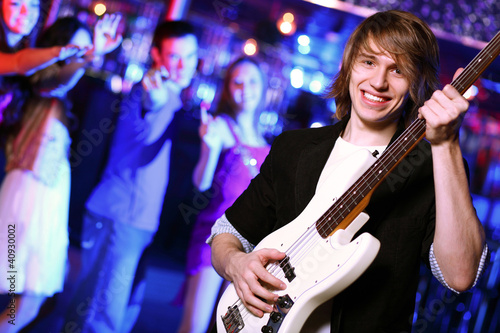 Fotobehang Muziek Young guitar player performing in night club