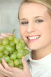 Young woman with a bunch of green grapes