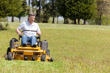 Senior man on zero turn lawn mower on turf