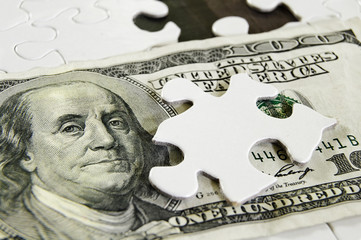 Closeup of a US $100 bill and puzzle piece