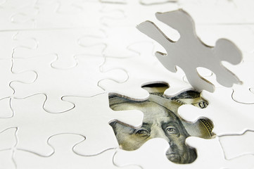 white puzzle pieces and US money