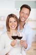 glückliches junges paar trinkt rotwein