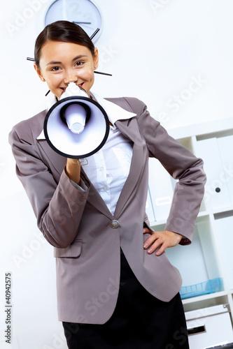 mladá žena s megafonem v kanceláři