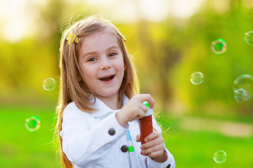Adorable little girl blowing soap bubbles